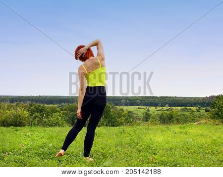 Sports exercising doing woman outdoors, on grass. The concept of a healthy lifestyle.
