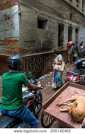 VARANASI INDIA - MARCH 13 2016: Vertical picture of indian people trying to move in a narrow dirty street of Varanasi in India