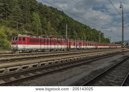 Red fast train in Slovakia station Ruzomberok in summer sunny day