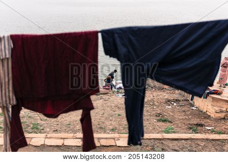 VARANASI INDIA - MARCH 13 2016: Horizontal picture of two india men washing clothes in Parakota Ghat at Ganges River in the city of Varanasi in India