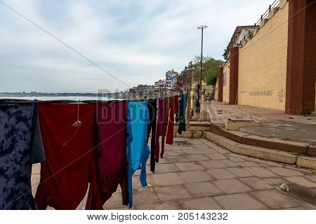 VARANASI INDIA - MARCH 13 2016: Wide angle picture of the washed colorful clothes at Parakota Ghat in front of Ganges River in the city of Varanasi in India