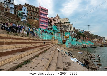 VARANASI INDIA - MARCH 13 2016: Horizontal picture of the stairs and houses at Lal Ghat in front of Ganges River in the city of Varanasi in India
