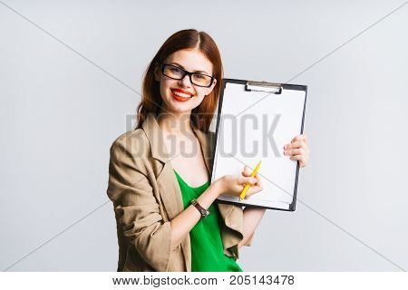 Smiling girl in glasses suit shows something on sheet a4, space for information