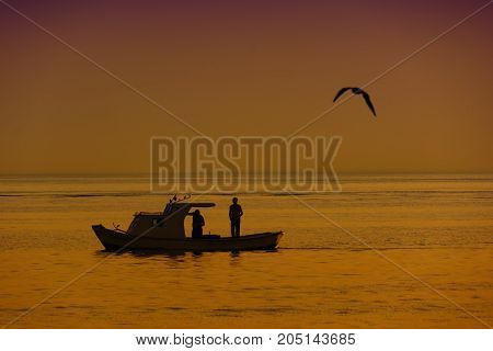 fisherman and boat on sea with seagull sillhouette landscape photography
