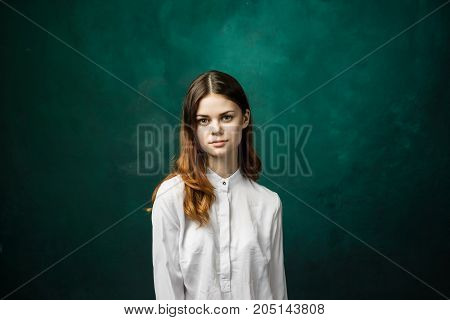 Girl student in a white shirt on a green background