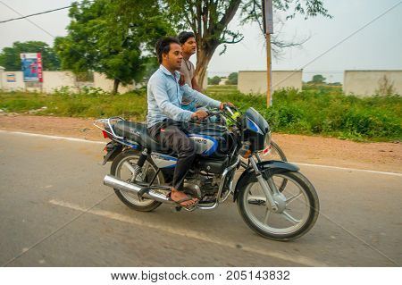 AGRA, INDIA - SEPTEMBER 19, 2017: Unidentified men rides a motorcycle and his friend a byke in the streets in central India in Agra, India.