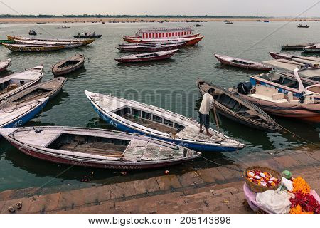 VARANASI INDIA - MARCH 13 2016: Horizontal picture of many docked boats and a indian man at Ganges River in the city of Varanasi in India