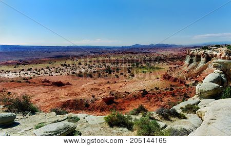 Desert Rocks and Cliffs. Red sand with dark mountains on the horizon.
