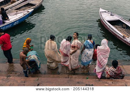 VARANASI INDIA - MARCH 13 2016: Horizontal picture of indian people bathing at the holy Ganges River in the city of Varanasi in India