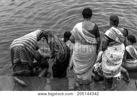 VARANASI INDIA - MARCH 13 2016: Black and white picture of indian women with traditional clothes bathing at the holy Ganges River in the city of Varanasi in India