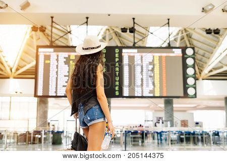 The unrecognizable traveler girl stands with her back and looks at her flight on the scoreboard with a timetable