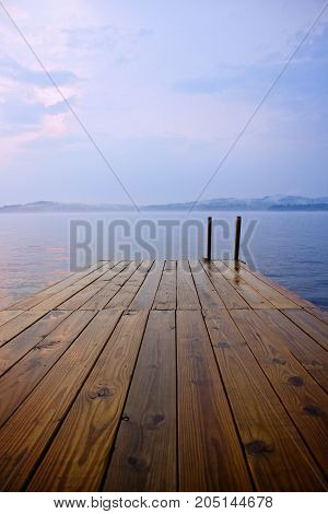 A wooden dock by a lake at sunset.