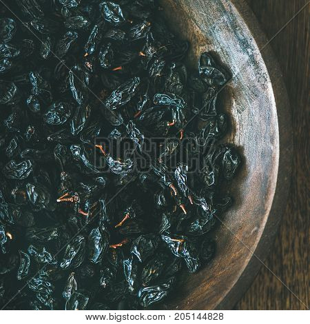 Black dried raisins in vintage plate over rustic wooden background, top view, square crop