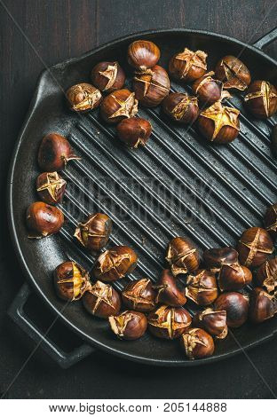 Roasted chestnuts in cast iron grilling pan over dark scorched wooden background, top view, copy space, vertical composition
