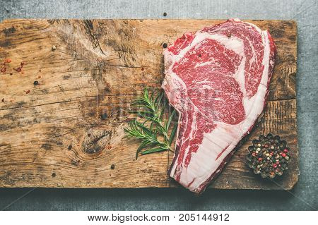 Flat-lay of raw uncooked prime beef meat dry-aged steak rib-eye with seasoning on rustic wooden cutting board over grey concrete background, top view, copy space. Meat high-protein dinner concept