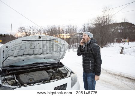A man on the winter road is calling the phone near the car