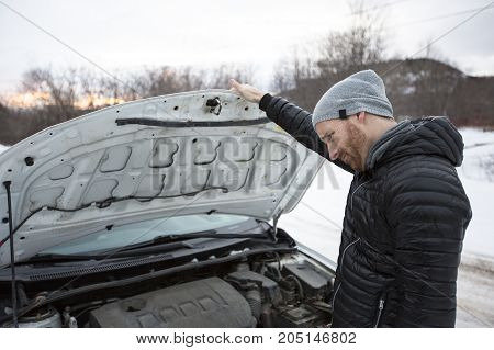 A Man problem close to the broken car in winter