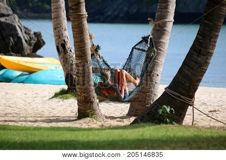 Tourists girls relaxing and lying on a hammock on the beachSamui island Thailand.