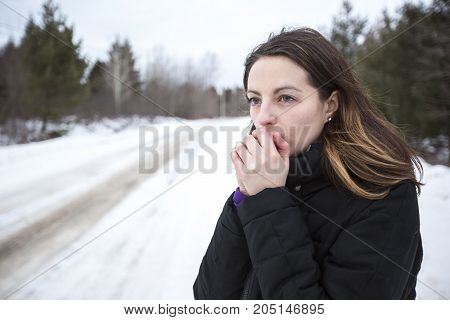 A Girl warms her hands by breath in winter season