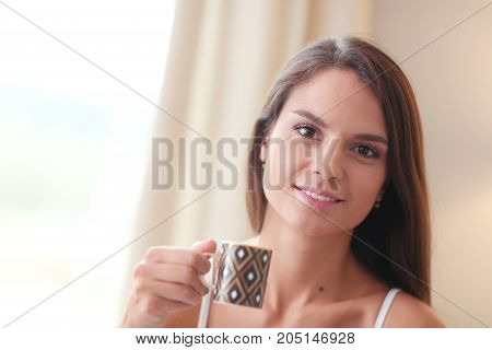 Young woman sitting in bed with a cup of milk.