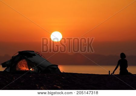 Silhouette of a woman camping with tents on the beach Red sky sunset background