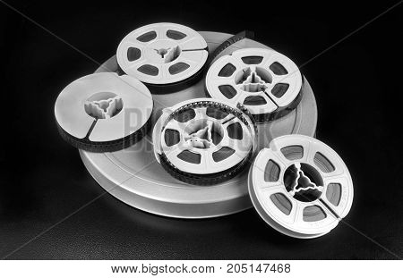Old time 8mm film and film canisters in black and white.