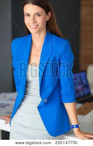 Portrait of a beautiful business woman standing near her workplace