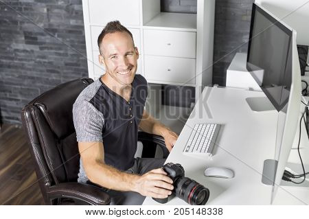 A Handsome photographer with camera at office with computer on the front
