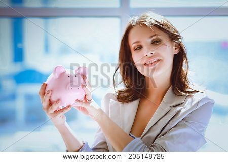 Young beautiful woman standing with piggy bank money box, isolated on white background.