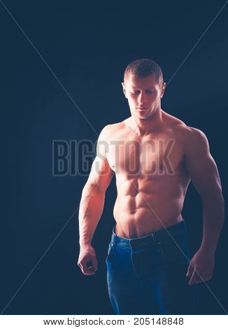 Strong young athletic man on black background.