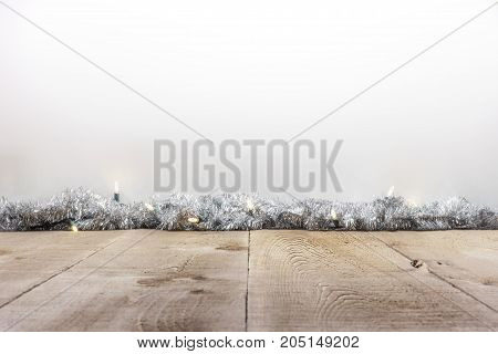 Rustic Wood Table Or Surface With Holiday Lights And Tinsel, White Space For Text