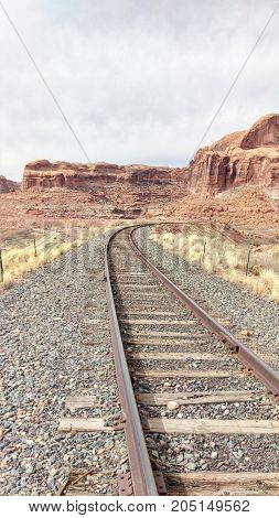 A Railroad winding around a landscape filled with red rock buttes.