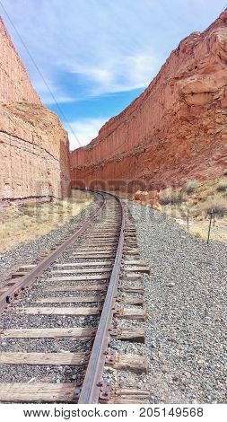 A rail road winding through red rock cliffs.