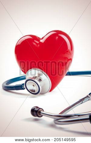 Red heart and a stethoscope on desk.