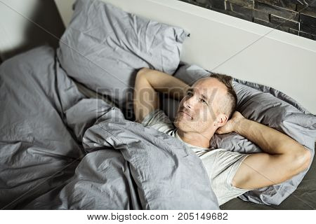 A Portrait of a young man from above sleeping in a bed.