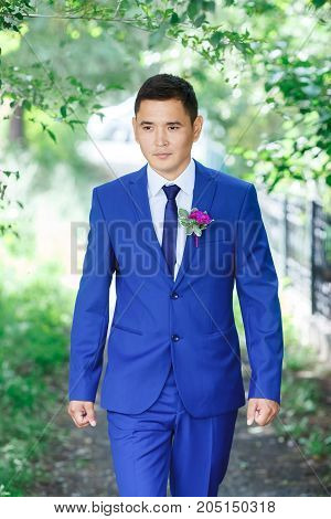 Male model, the groom in a blue suit with a boutonniere among the green foliage on a wedding day.