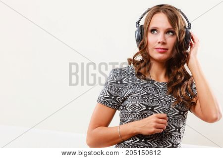 People leisure relax concept. Young woman in big headphones listening music mp3 relaxing at home