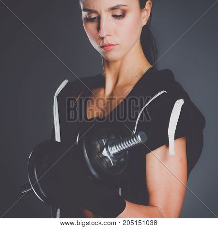Young woman doing exercise with dumbbells isolated on dark background