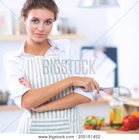 Smiling young woman standing  in the kitchen .