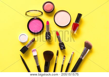 Cosmetics and fashion background with make up artist objects: lipstick eye shadows mascara eyeliner concealer nail polish yellow colorful background. Lifestyle Concept