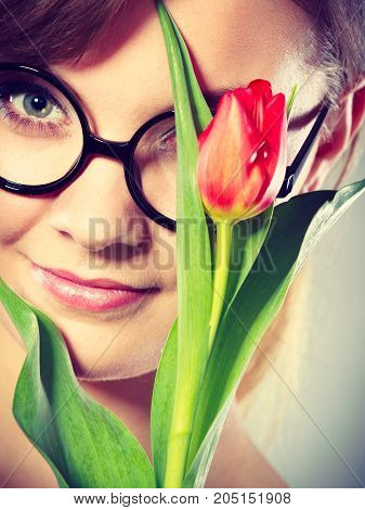 Fun casual flora nature beauty feminine concept. Cheerful girl with flower. Attractive lady in glasses holding tulip to her face.
