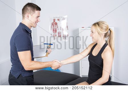 A male physio therapist and woman helping patient