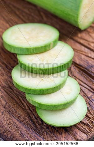 Preparing vegetable dish. Zucchini and zucchini slices on a wooden cutting board vertical closeup