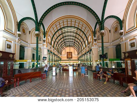Ho Chi Minh City, Vietnam - September 15th, 2017: Tourists visit Interior of Saigon Central Post Office. It was built by the French in 1886 and is now a tourist attraction Popular in Ho Chi Minh city, Vietnam.