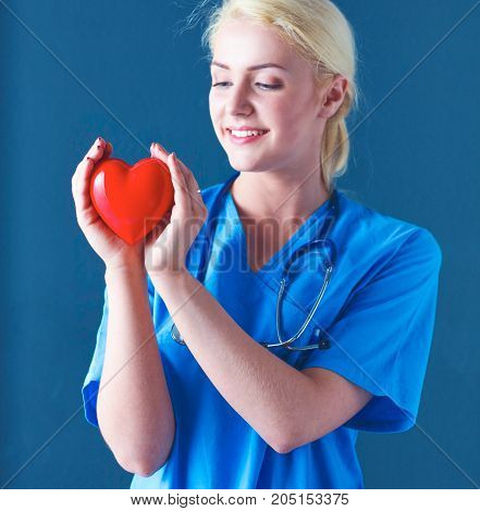 Doctor with stethoscope holding heart, isolated on gray background.
