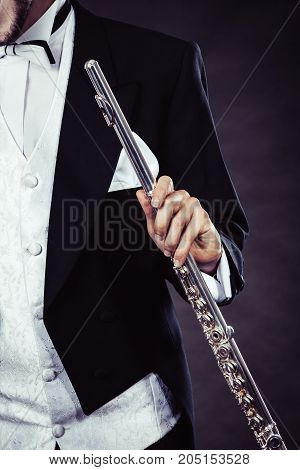 Classical music passion and hobby concept. Elegantly dressed musician man holding flute. Studio shot on dark background