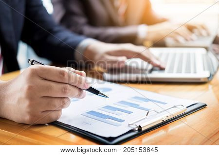 Businessman team working at office desk and using a digital computer laptop hands detail computer and objects on the table