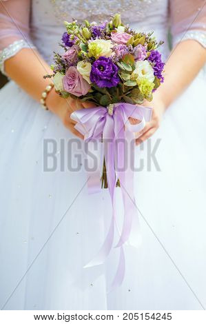 Bride in white dress holding purple wedding bouquet in hands closeup. Marriage concept
