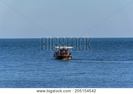 Wooden boat used to transport tourists in the Blach Sea. A group of tourists on a whale watching trip in the Black Sea near Tomis harbour, Constanta Romania.