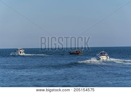 Three boats moving through the blue wather. Luxury private motor yacht under way on Black Sea sea with bow wave. People ride in wooden boat.